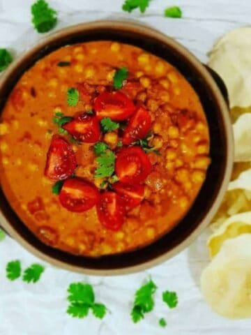 Chana Masala in a black bowl with coriander on top