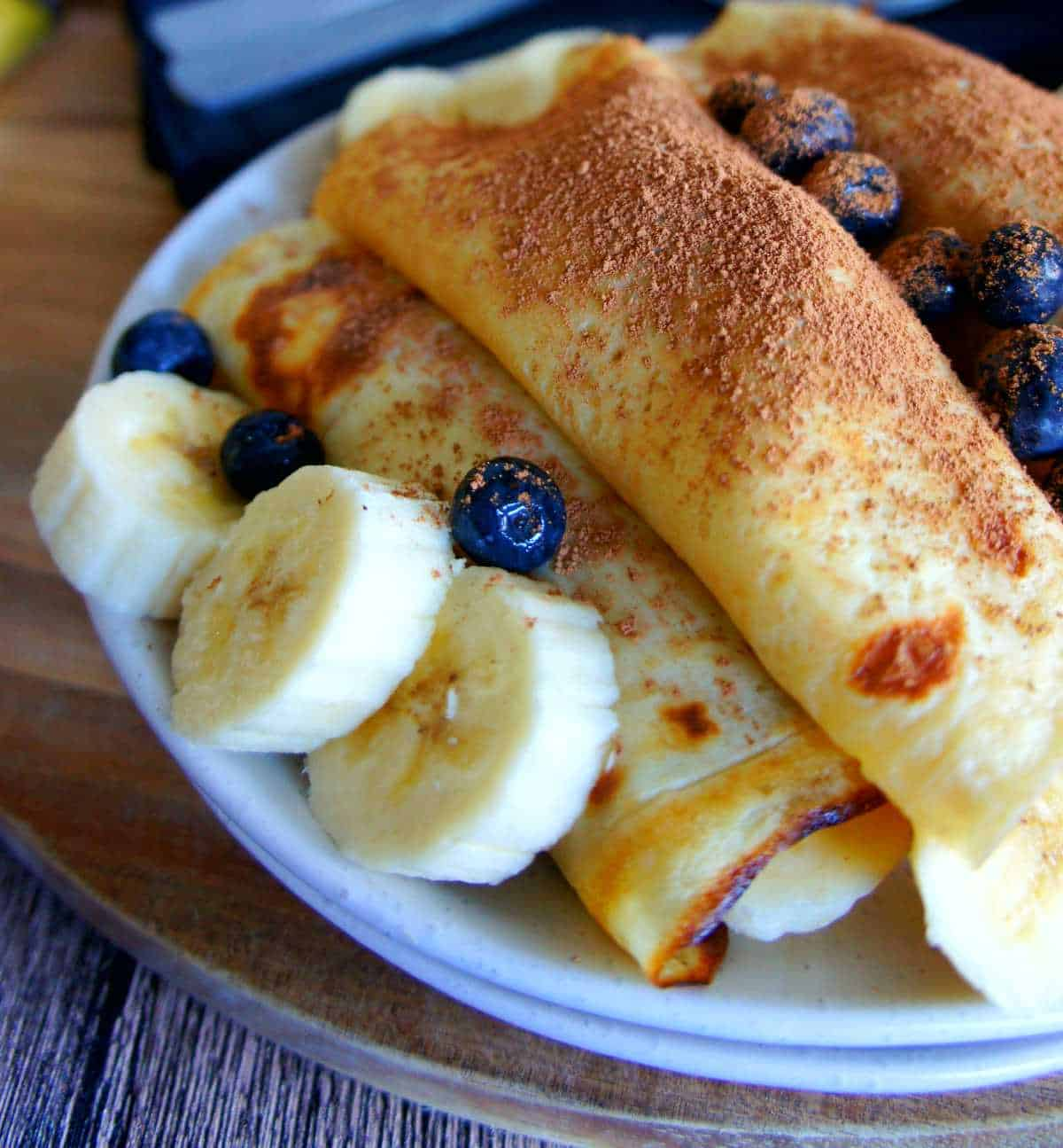 Blueberry crepes with banana and custard on a white plate