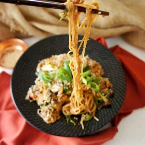 Vegan Brown Rice Noodles in chopsticks over a black plate