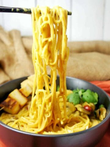 Yellow Curry Noodles held above bowl with chopsticks