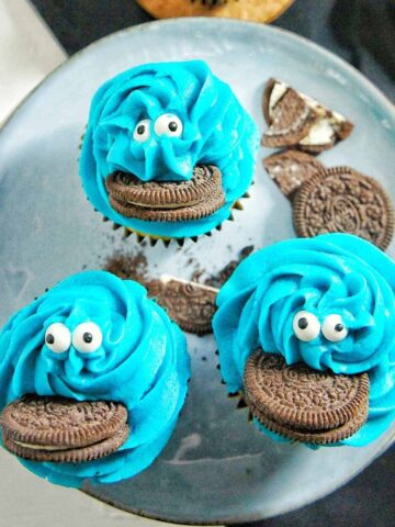 3 Cookie Monster Cupcakes on a blue plate with a black napkin underneath