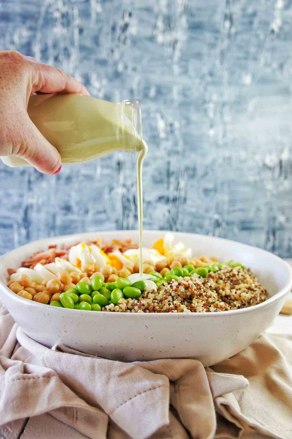 Edamame Quinoa Salad in a white bowl with the dressing being poured into it