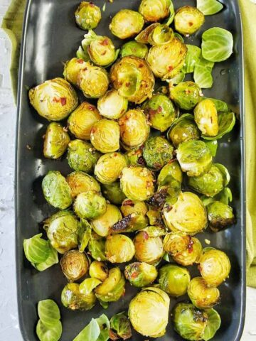 Roasted Brussel Sprouts on a black serving plate