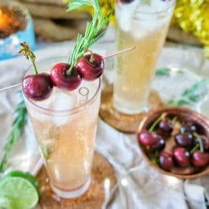 Christmas Cocktail with fresh cherries on top of tall glasses