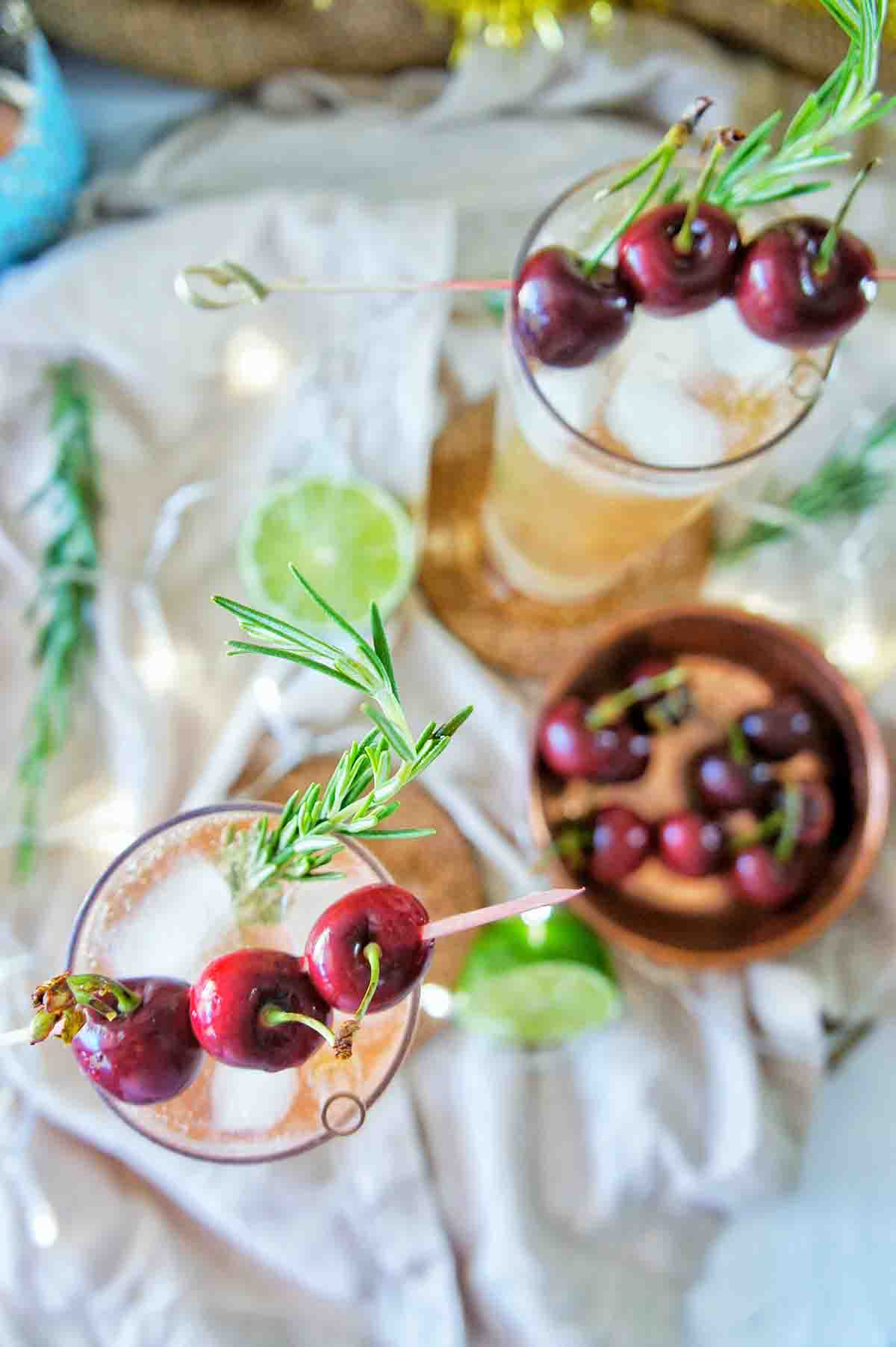Christmas Cocktail in tall glasses with fresh rosemary sprigs and cherries