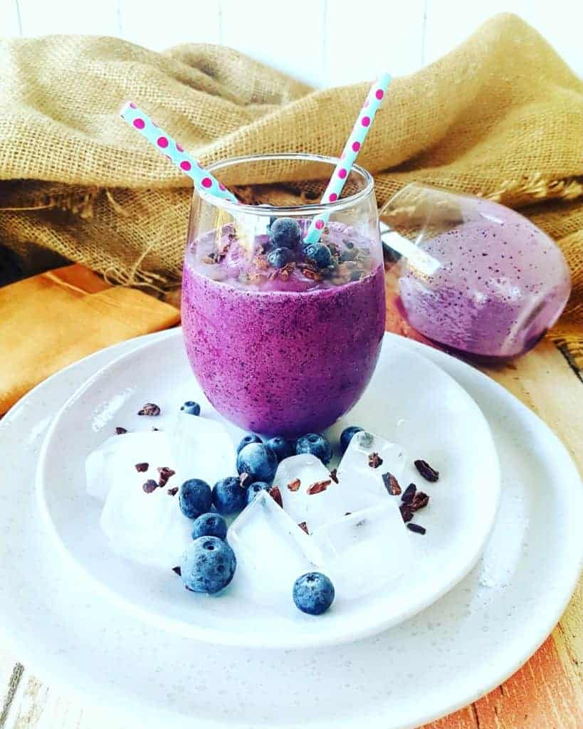 Blueberry Smoothie in a glass on a white plate with a blue straw