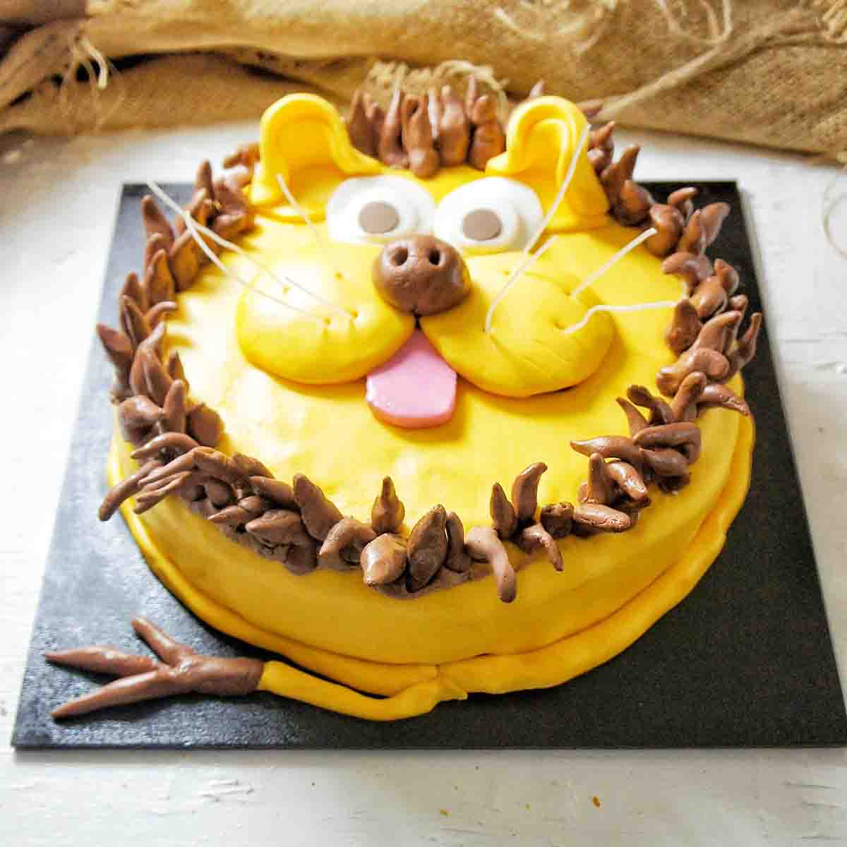 Lion cake on an angle on a black cake board