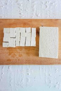 Tofu cut into cubes on a wooden chopping board