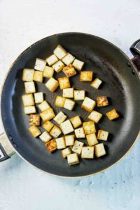 Fried tofu pieces in a large fry pan