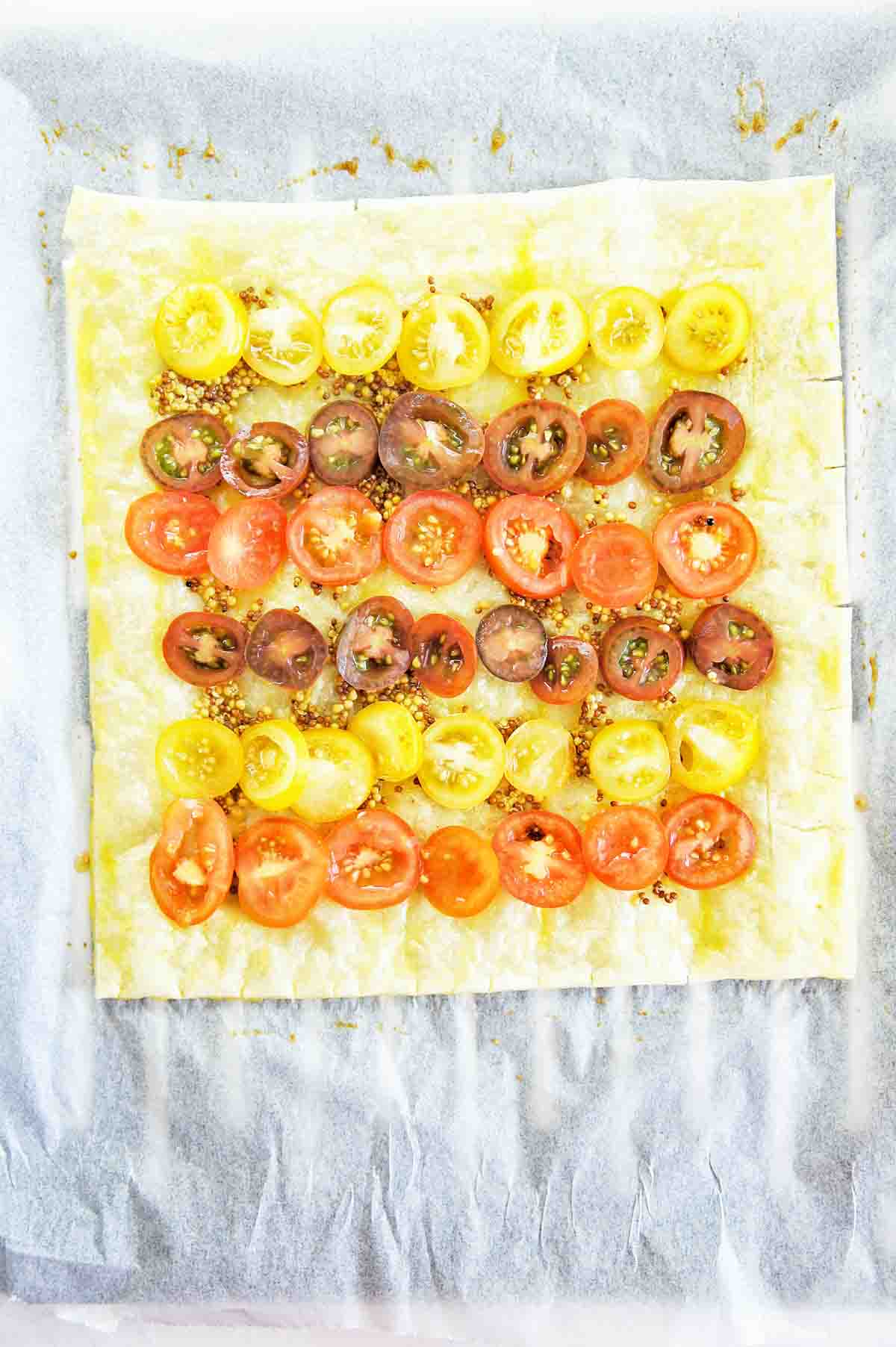 Pastry topped with heirloom tomatoes on a baking tray