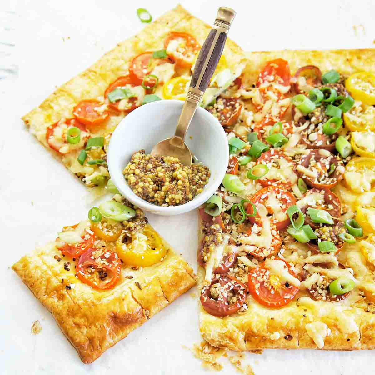 Tomato Tart with a small bowl of mustard that has a spoon in it on a white background