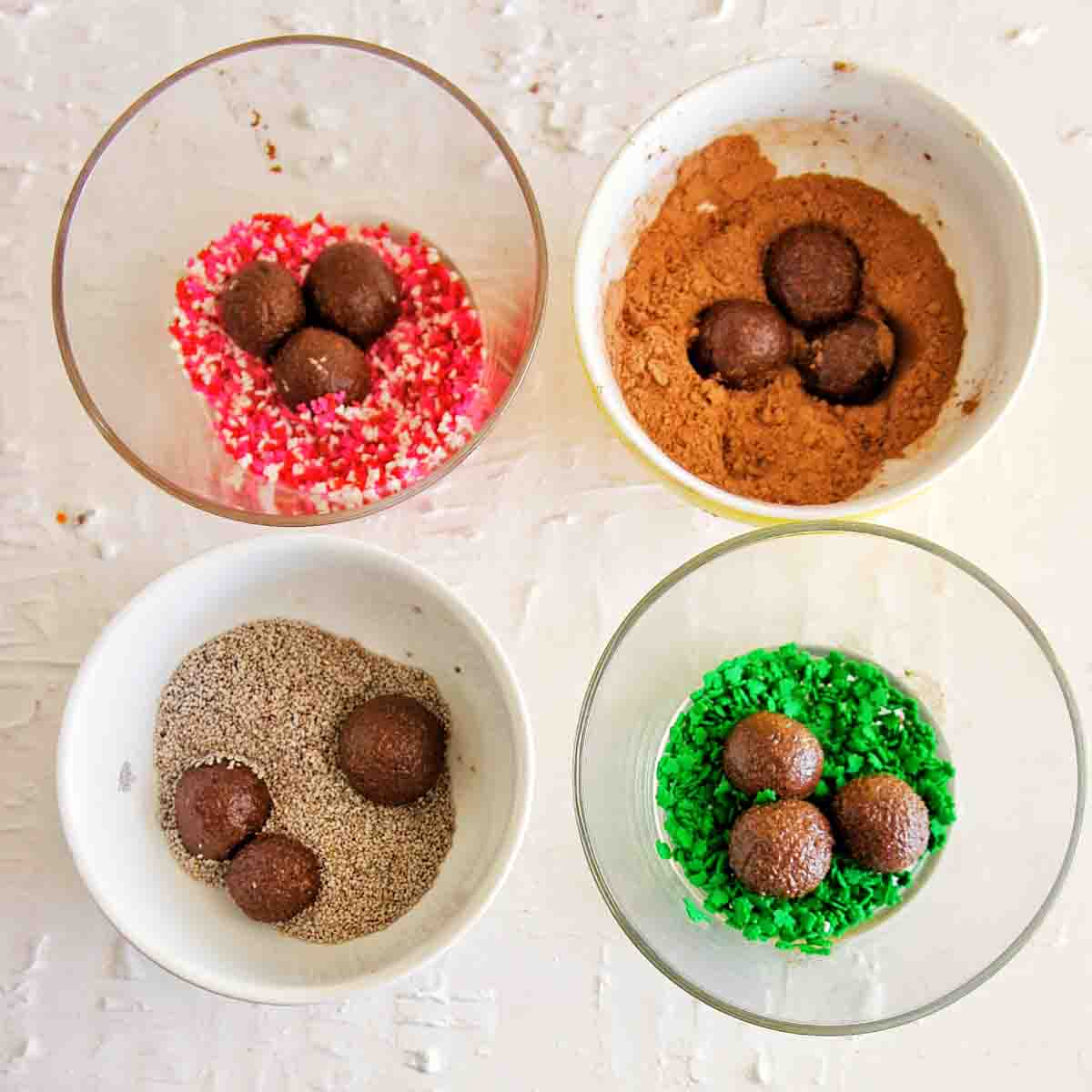 Four small bowls with sprinkles and chocolate balls in them