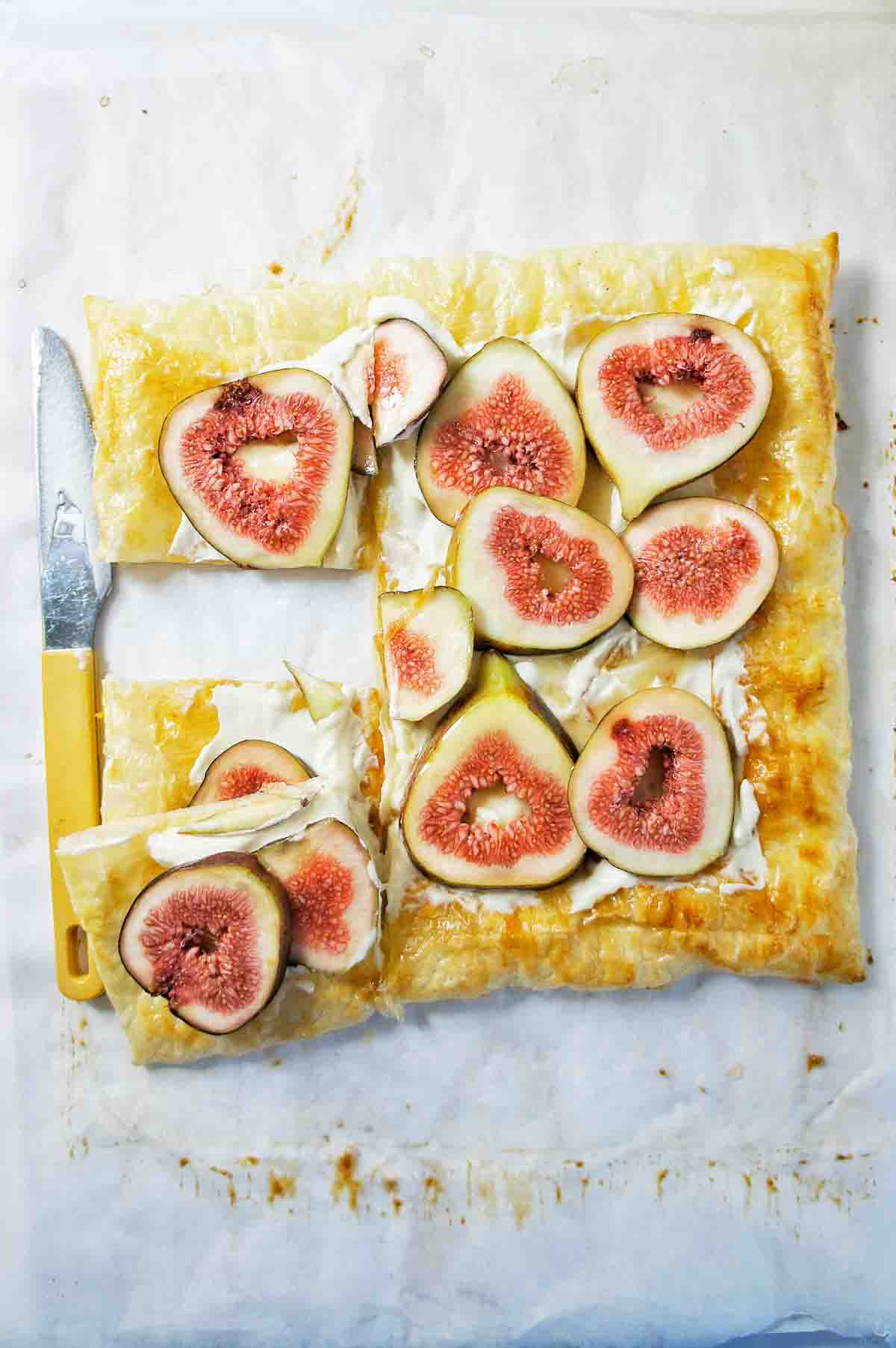 Fig Tart on a white background with a knife on the side