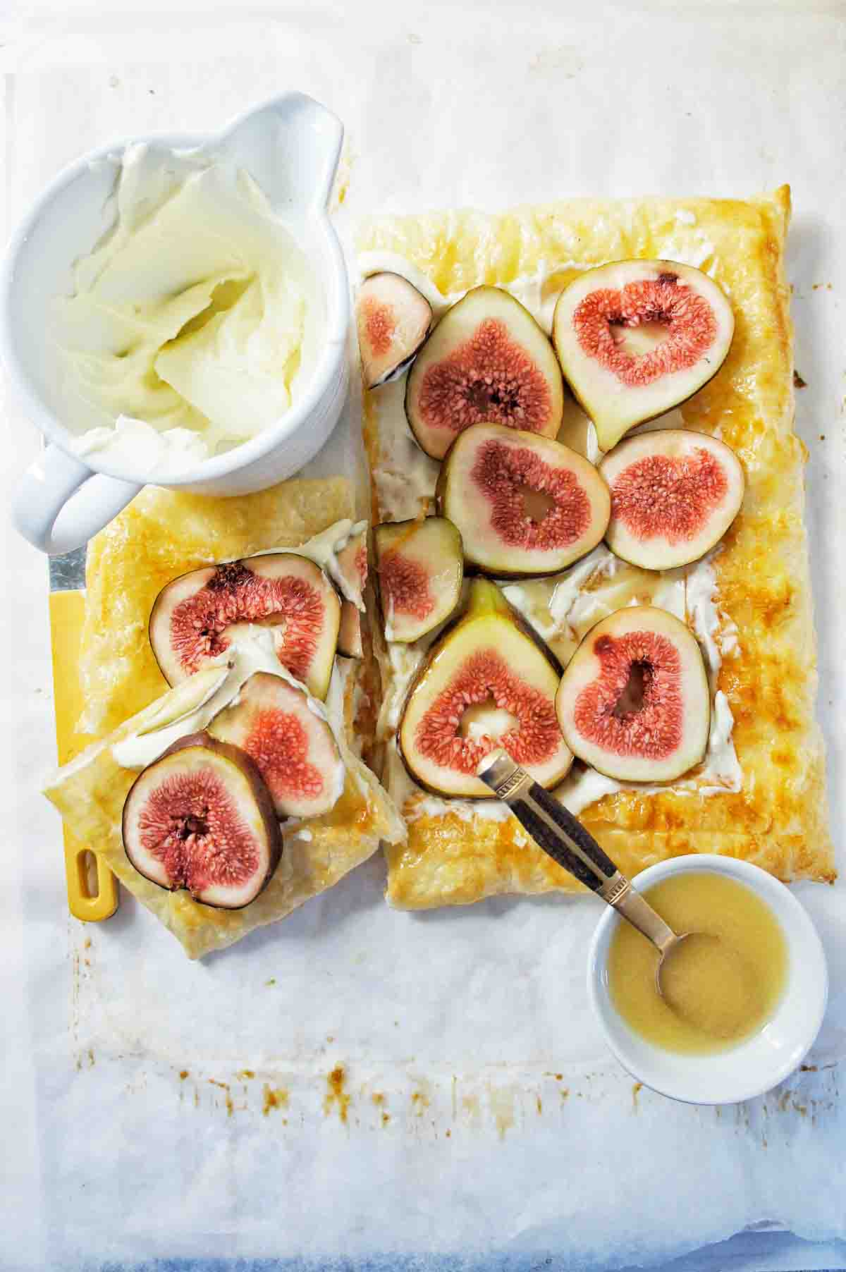 Fig Tart with cream in a jug and a small bowl of syrup with a spoon in it
