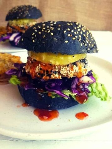 Pork Burger with a charcoal bun on a white plate