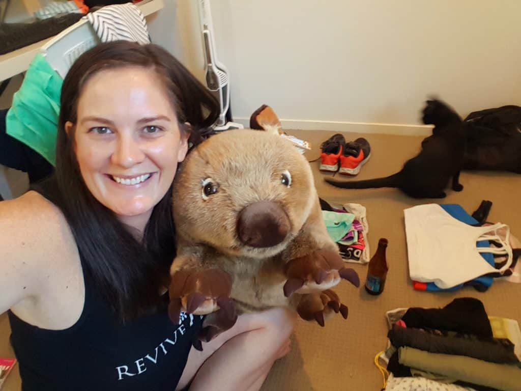 Girl packing for holiday with black cat in photo and stuffed wombat