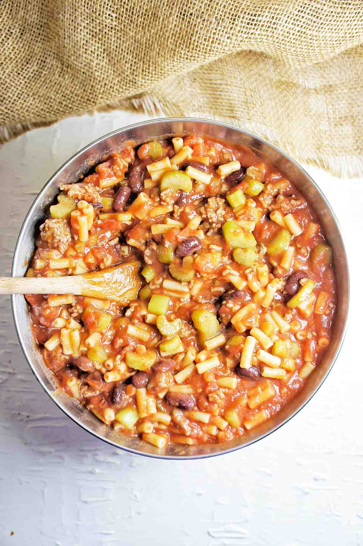 Beef beans macaroni with tomato sauce in a silver bowl