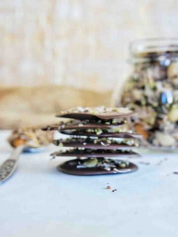 Chocolate Granola bark with blurred image of granola jar in the background