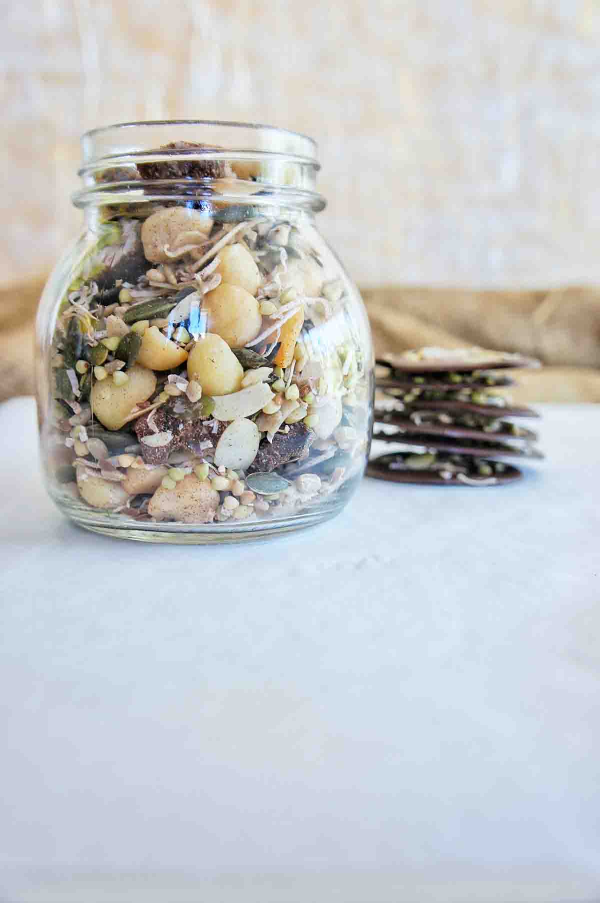 Chocolate Granola Bark with a focus on a glass jar with granola in it