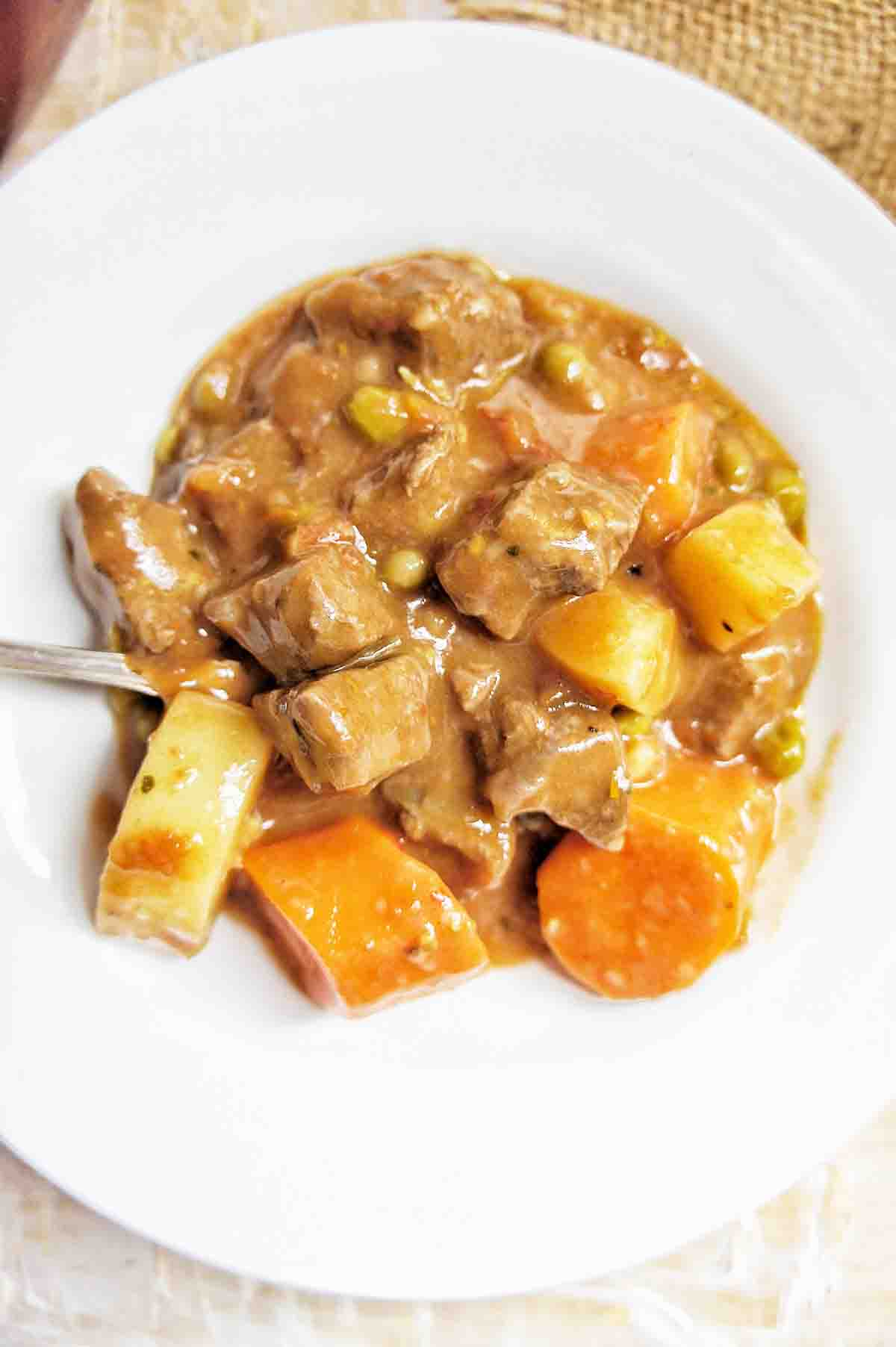 Easy Chunky Beef Stew in a white bowl with spoon to the left