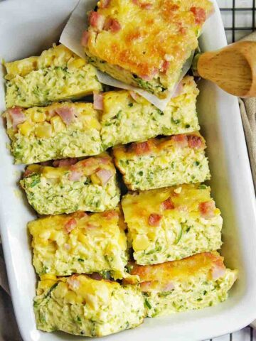 Gluten Free Zucchini Slice pieces in a white baking tray with small utensil on the side
