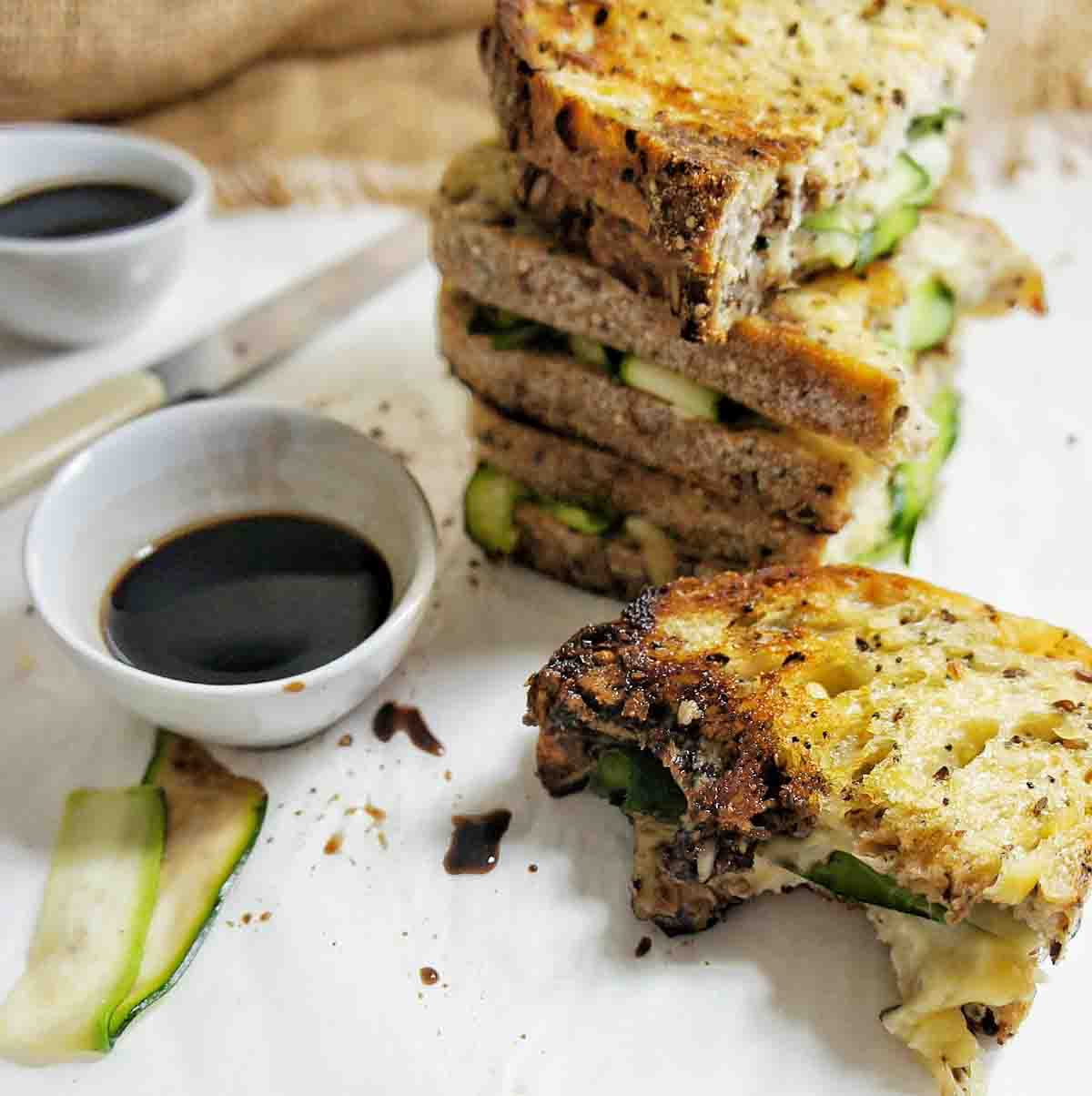 Corner of zucchini grilled cheese dipped in balsamic vinegar with sandwich stack behind