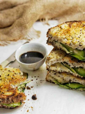 Cropped image of stack of zucchini grilled cheese sandwiches with one half to the left side