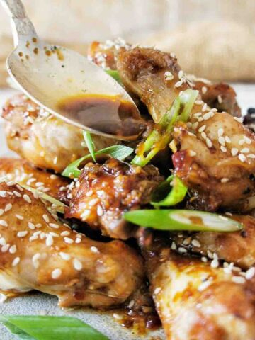 Spoon pouring sauce over honey soy chicken wings
