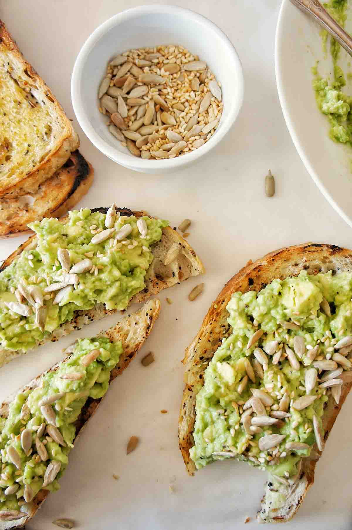 Avocado spread on toast with a small white bowl of seeds in the background