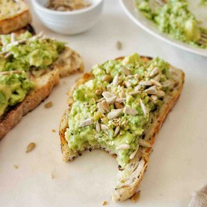 Simple Avocado Toast with a bite out of it on a white background