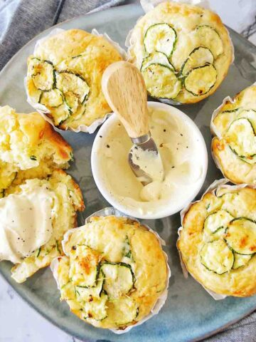 Zucchini Parmesan Muffins on a blue plate with mustard yoghurt