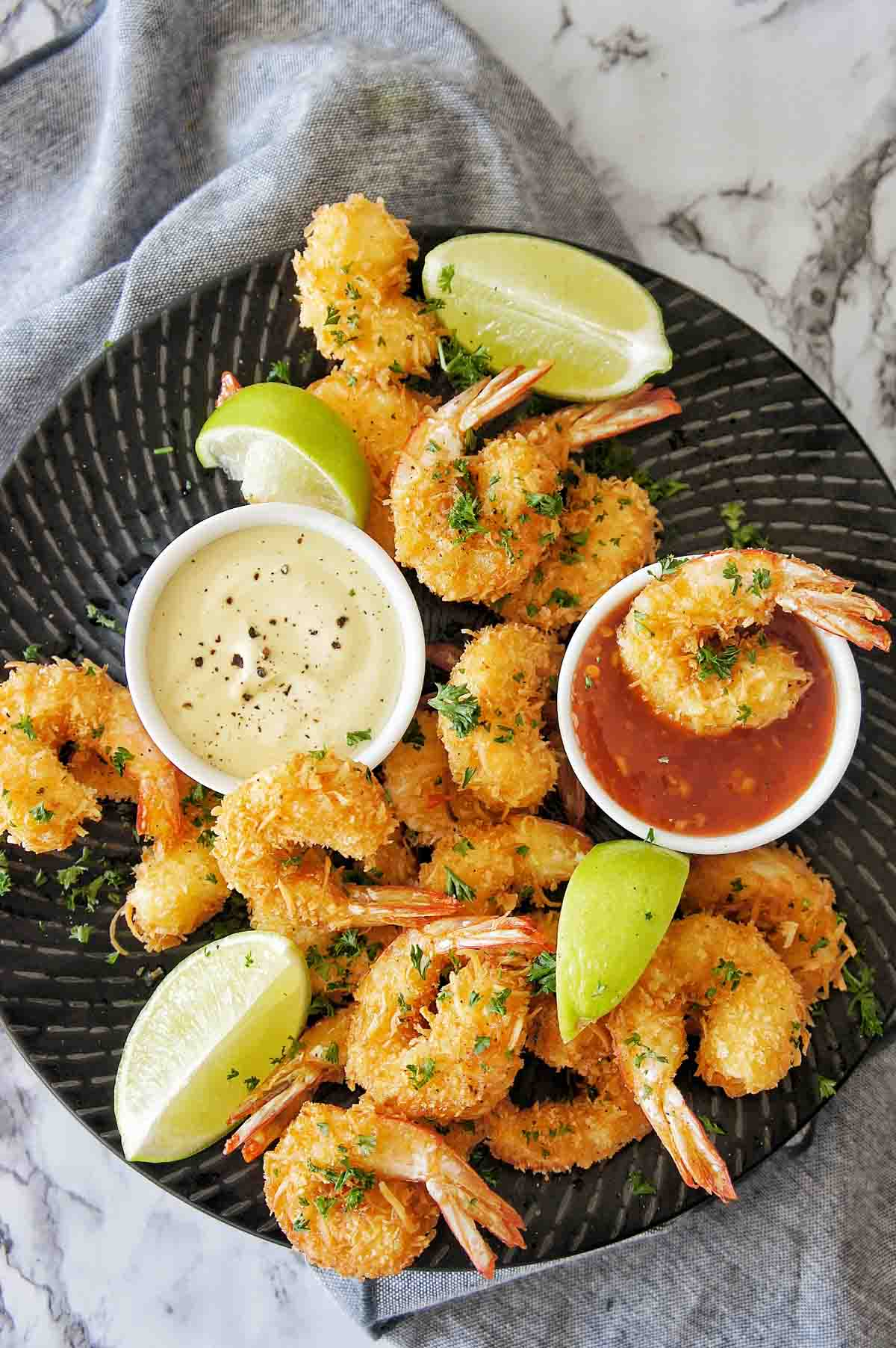 Coconut Prawns on black plate with 2 small bowls of dipping sauce