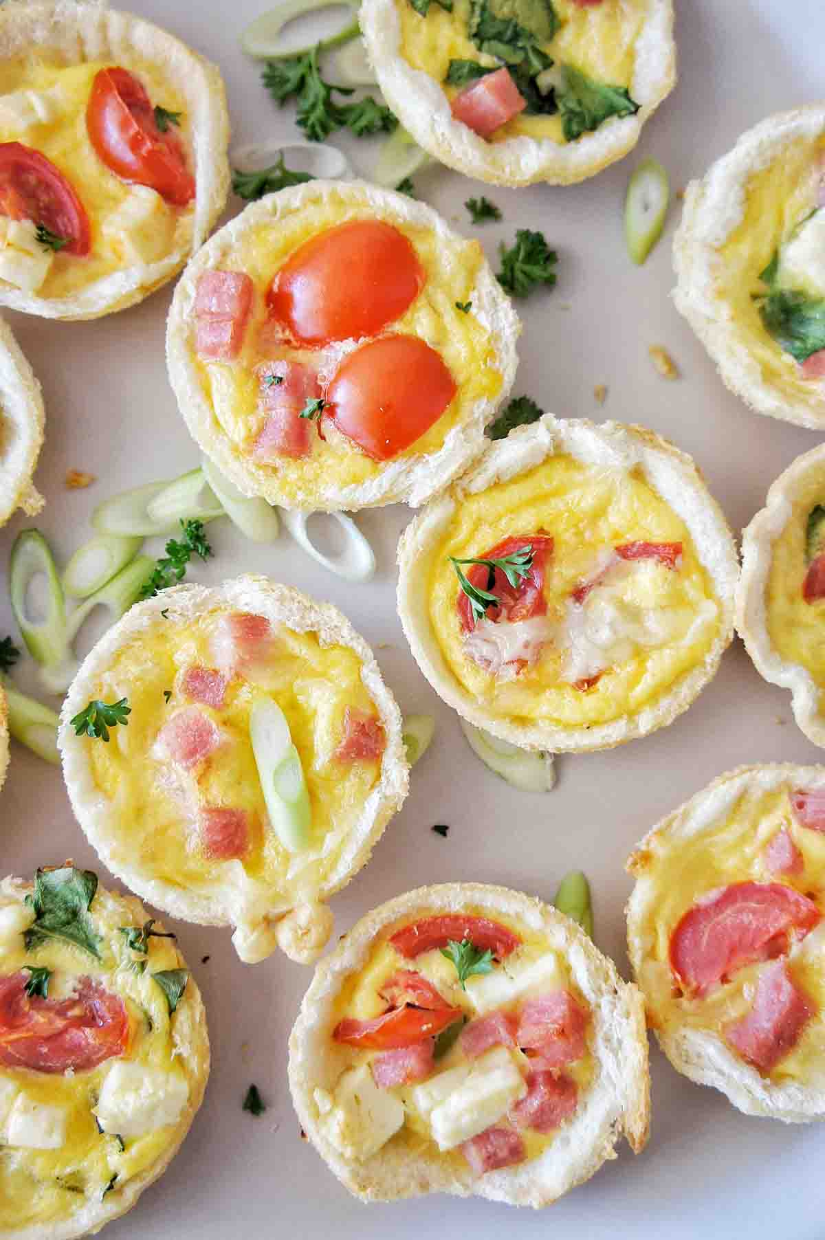 Mini quiches on a pale cream plate garnished with sliced shallots