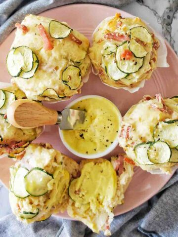 Zucchini and Ham Muffins on a pink plate with a yellow spread in the middle