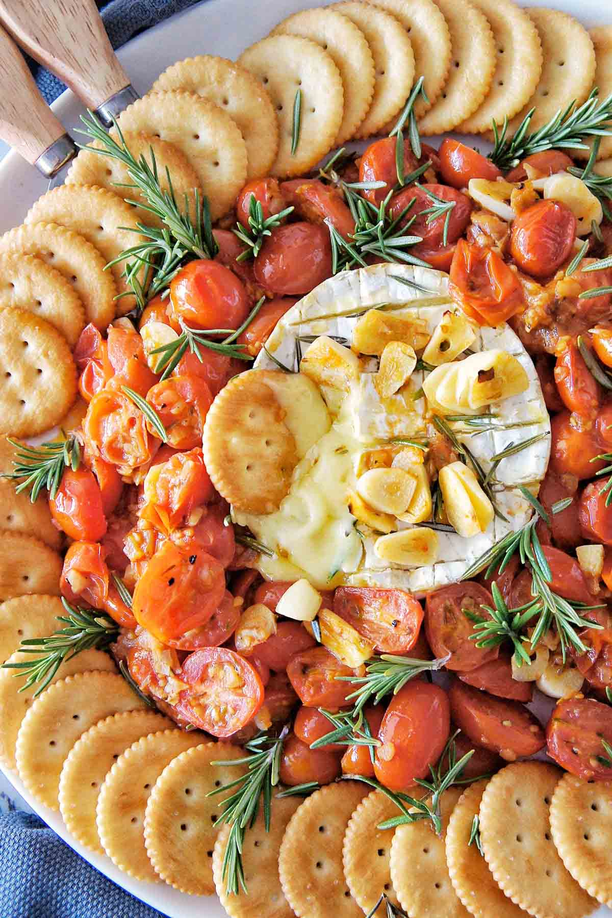 Baked brie with garlic surrounded by roasted tomatoes and crackers