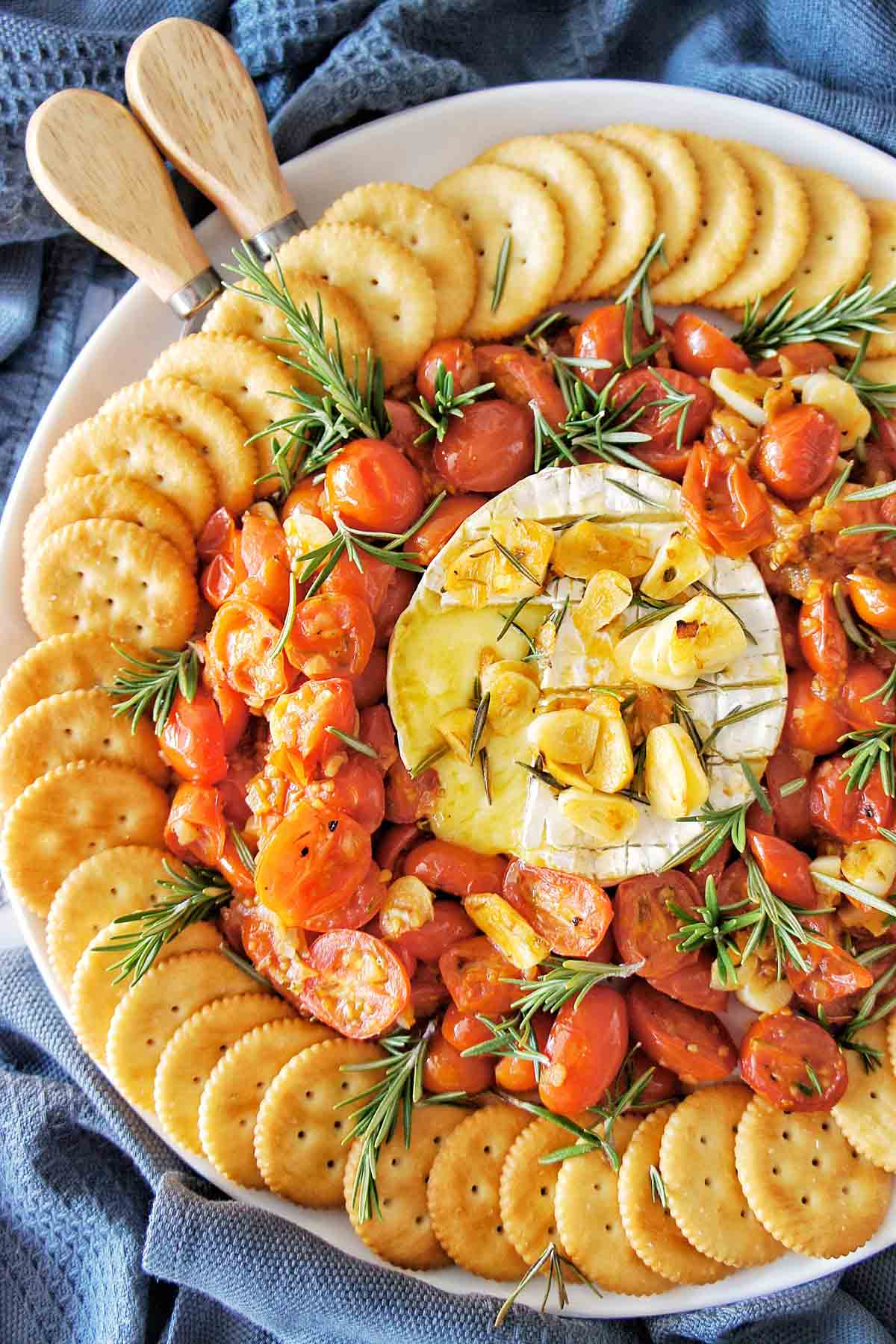 Baked Brie on a platter with roasted tomtatoes and crackers around the outside