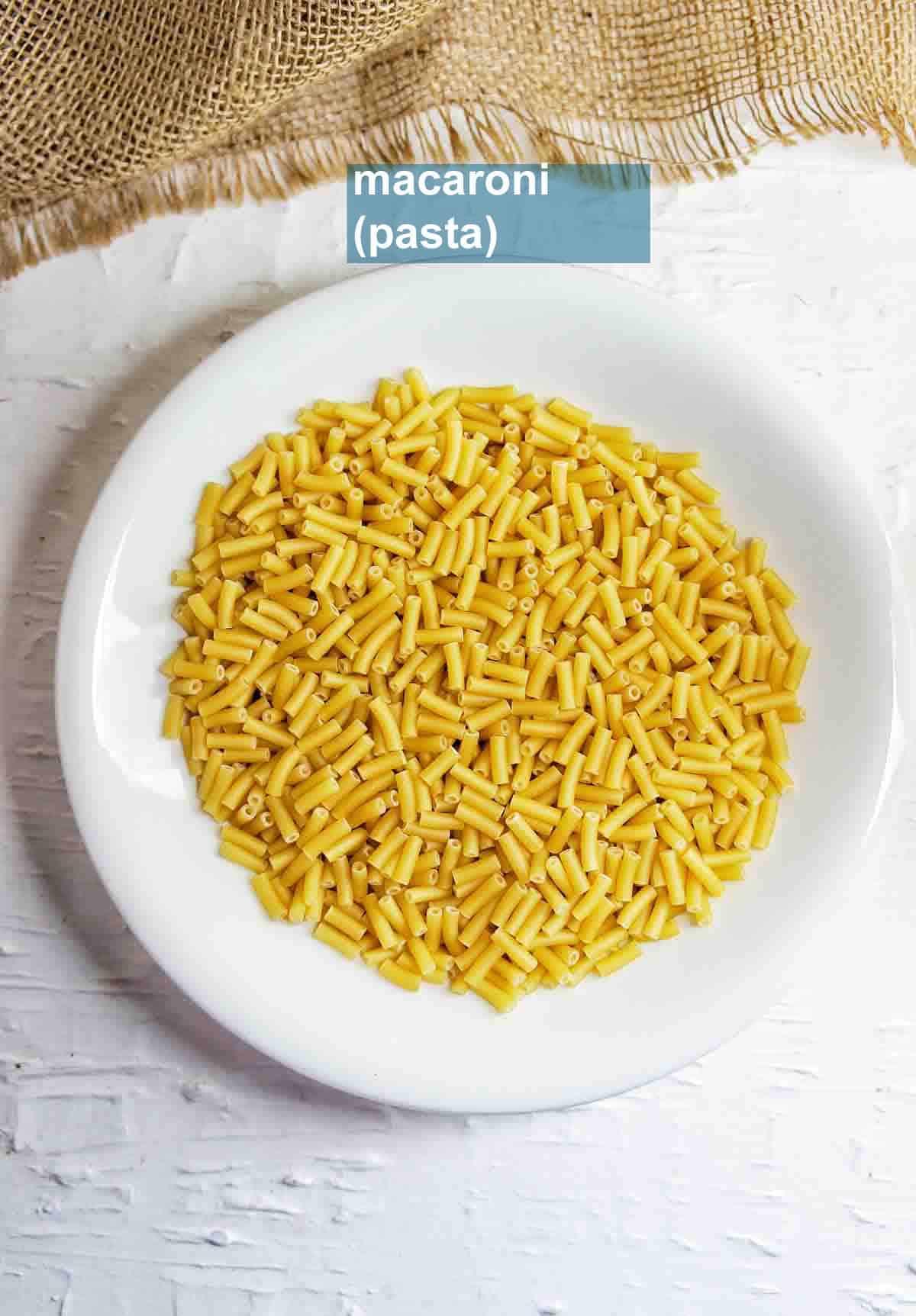 White bowl of dry uncooked macaroni pasta