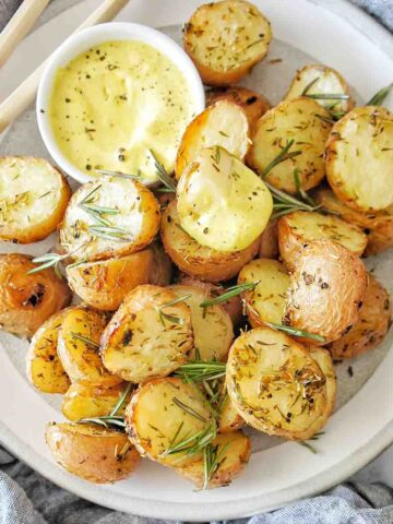 Skin on roast potatoes on a grey plate with a small white bowl with mustard