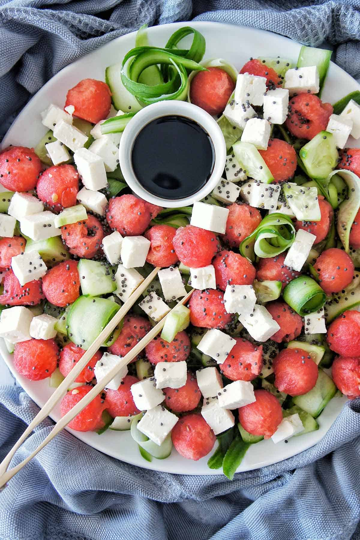 Watermelon cucumber salad with a small bowl of balsamic vinegar on a white plate