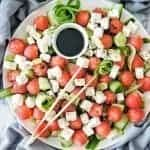 Watermelon Feta Cheese Cucumber Salad on a large white platter with a small bowl of balsamic vinegar