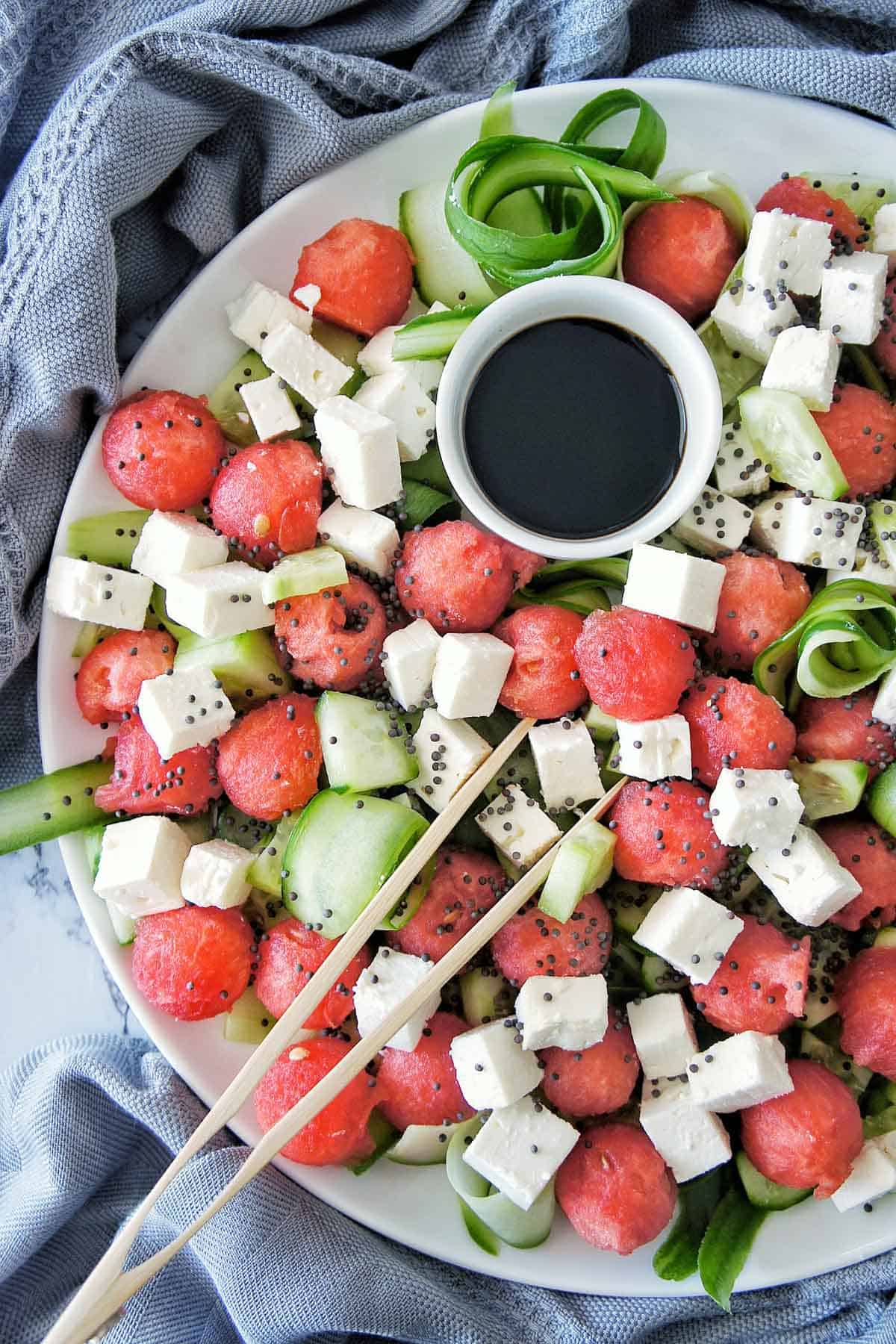 Watermelon Cucumber Feta Salad on a white platter with small bowl of dark coloured dressing