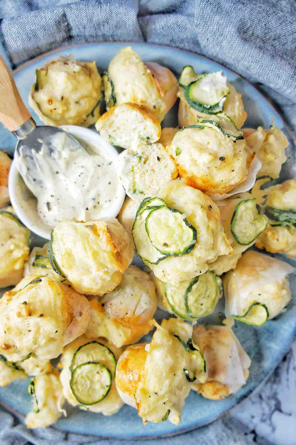 Mini Zucchini Muffins on a blue plate with a small bowl of mustard yoghurt
