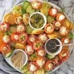 Caprese Bites with balsamic vinegar on large white platter