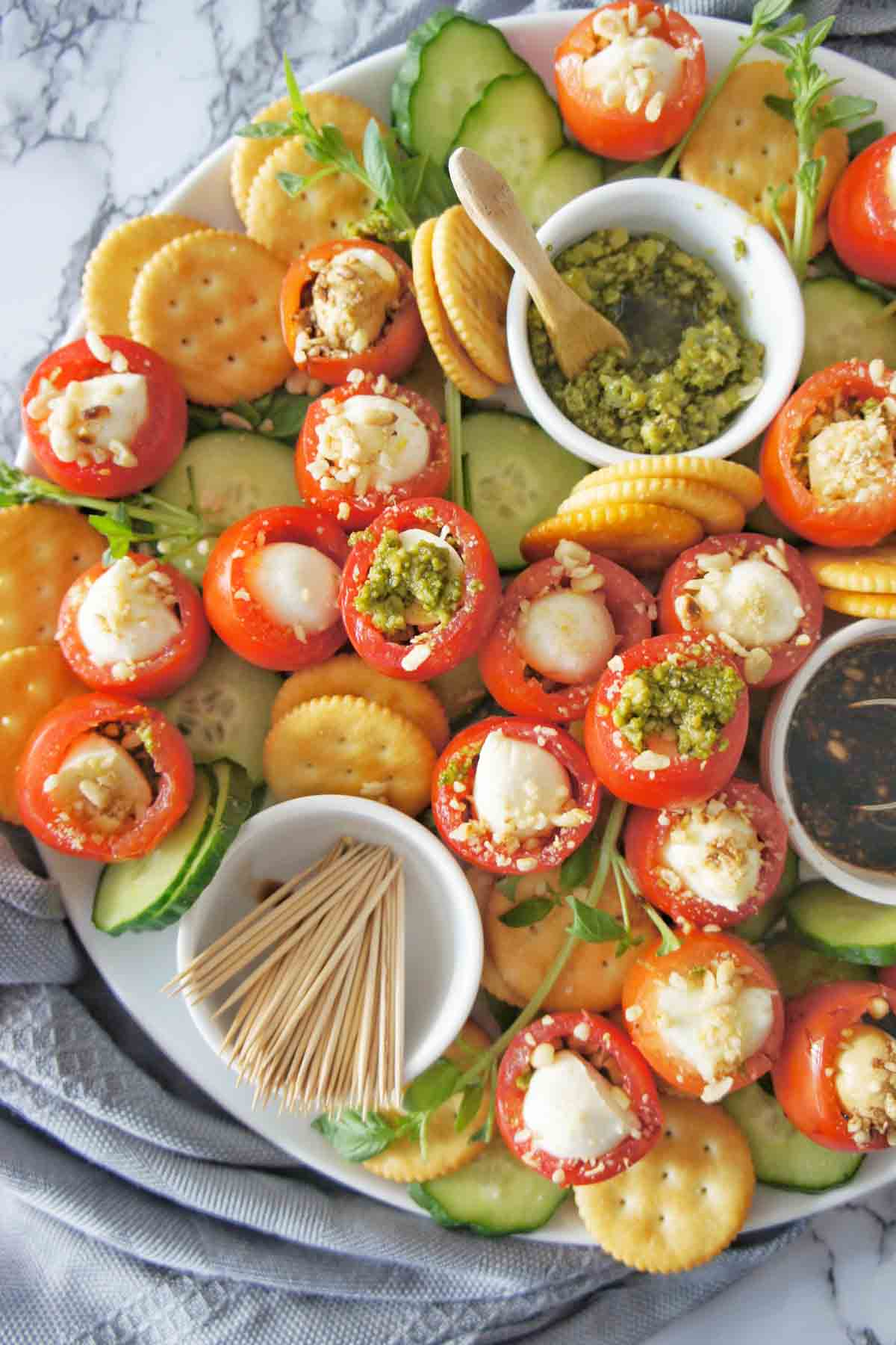 Caprese bites on a large white platter surrounded with small white bowls of dips and balsamic vinegar