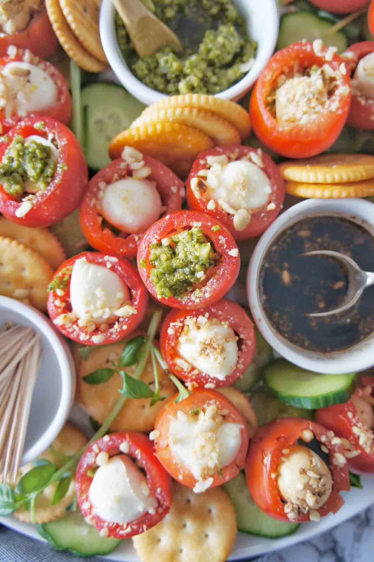 Caprese bites showing mozzarella in tomatoes with basil pesto