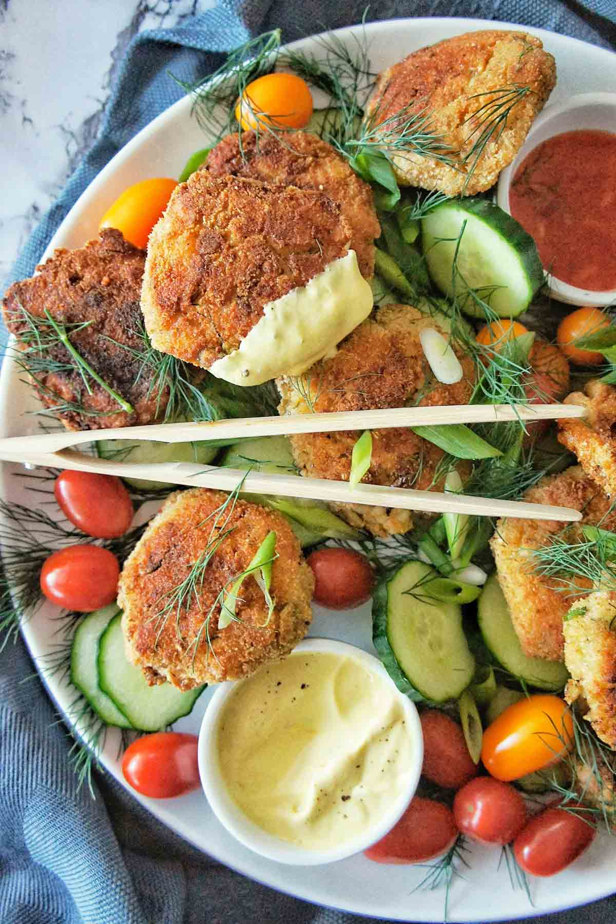Crab cake that has been dipped in yellow sauce and place on a platter with salad and serving tongs