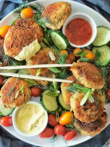 Crab cakes on a white platter with salad and a small bowl of crab cakes sauce