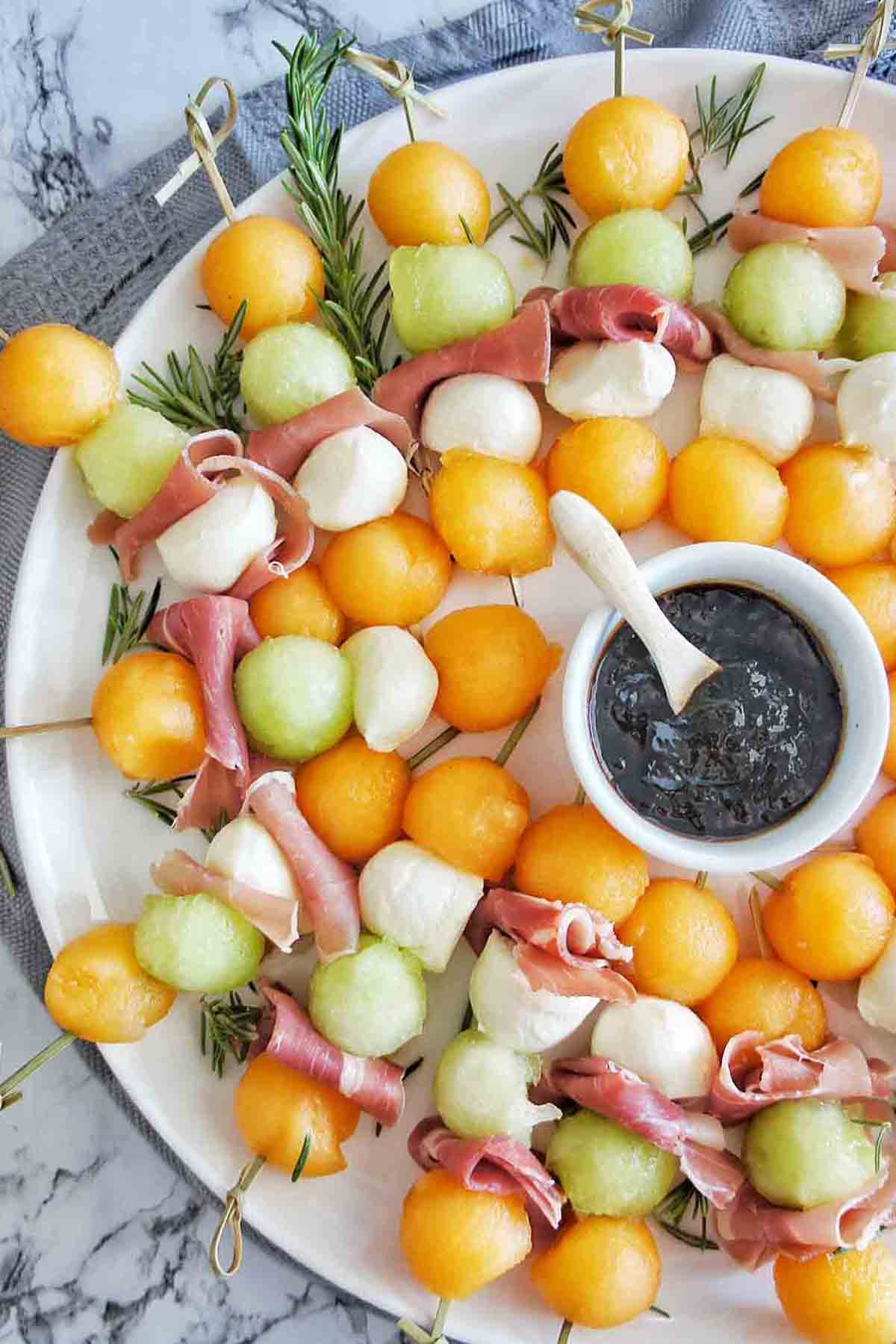 Melon and Prosciutto skewer platter with small bowl of balsamic glaze