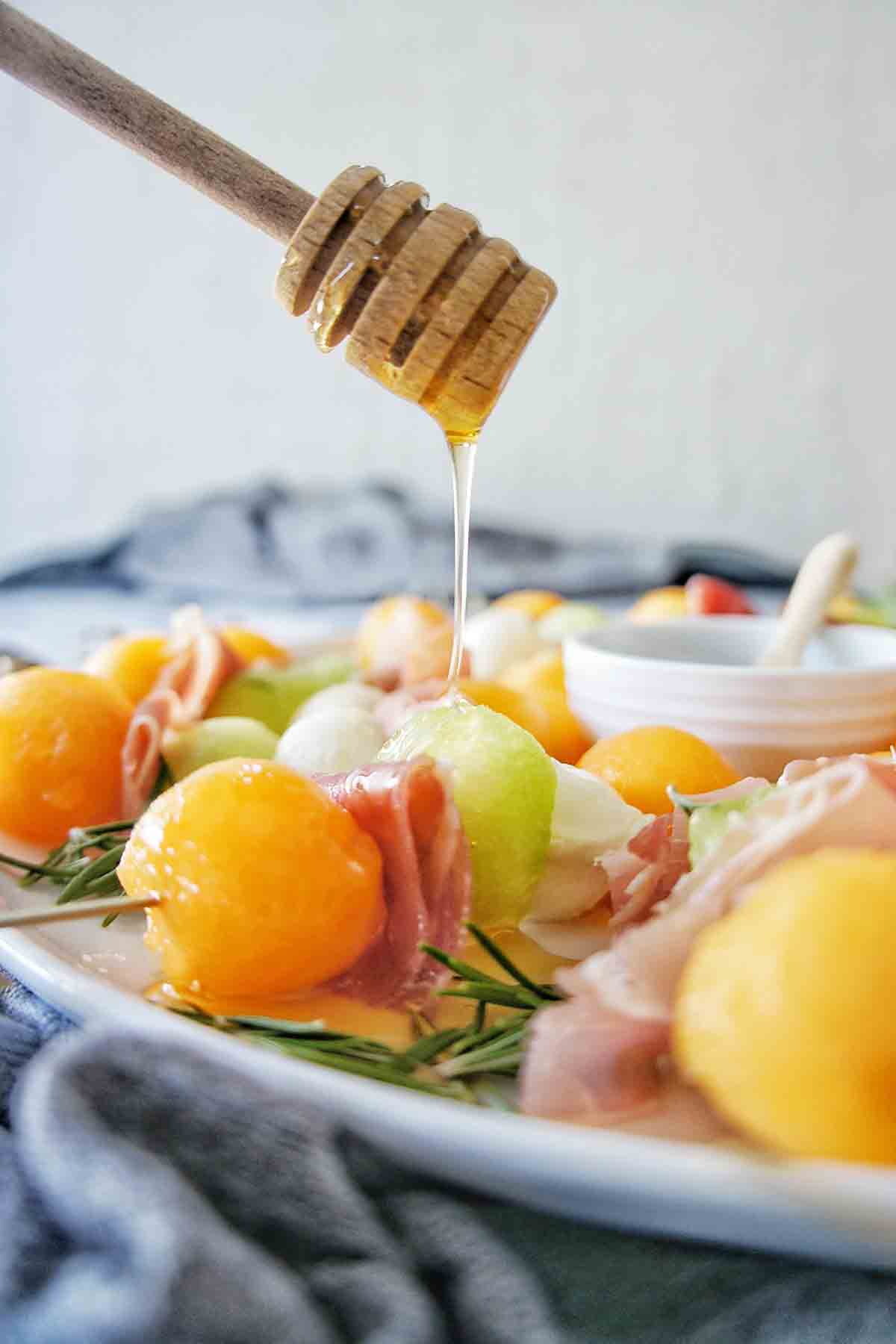 Honey being drizzled over Melon and Prosciutto skewers