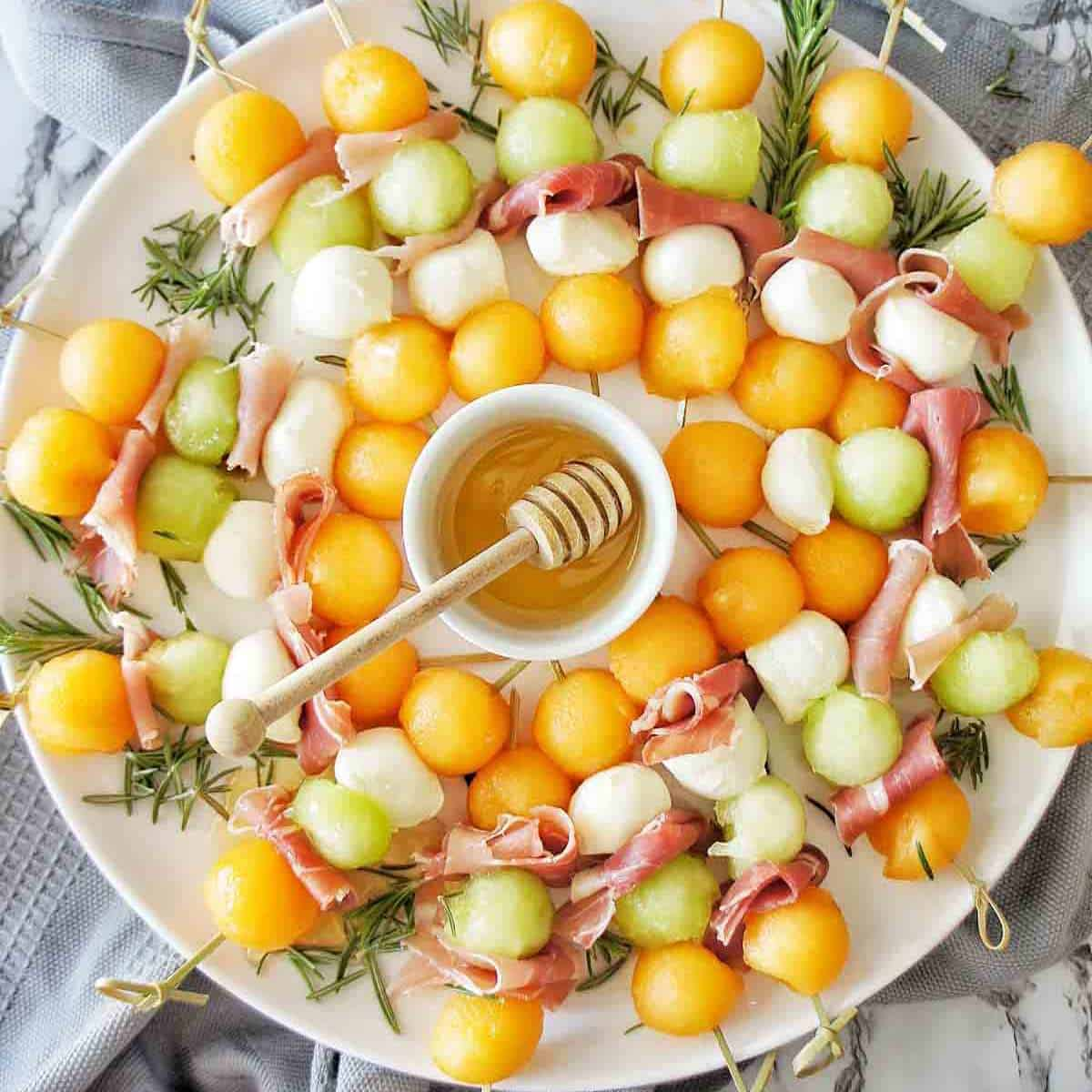 Melon and Proscuitto skewers on platter with small white bowl of honey in the middle